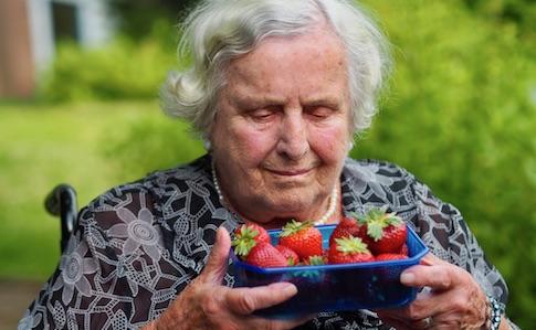 Bewohnerin des Tobias-Hauses genießt den Duft frischer Erdbeeren